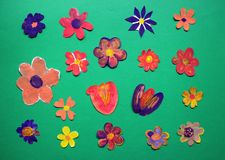 Different painted and cut flowers on green background stock photography