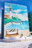 Beautiful painting of graffiti on the facade of a five-storey building in Russia. Winter. Drawing sea, lighthouse yacht, boat royalty free stock photography