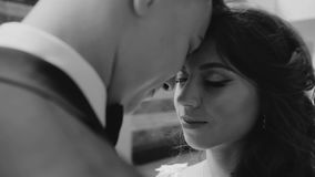 A beautiful pair of lovers, standing against each other`s foreheads. very nice close-up. black and white stock video