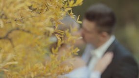 Beautiful pair of newlyweds near a bright yellow stock video footage