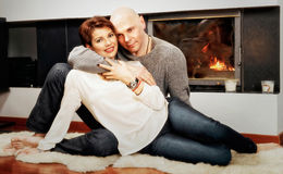 Beautiful pair sitting on fur carpet near the fireplace Royalty Free Stock Images