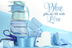 Beautiful pale aqua baby blue gift wrapping ribbons and gift boxes. On blue and white background with copy space for Fathers Day, Baby Boy shower or christening Royalty Free Stock Images