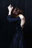 Beautiful pale thin woman in a heavy black silk taffeta dress. Is weeping on a stage, throwing her arms. She buried her face in her hands. She feels sadness and stock photo
