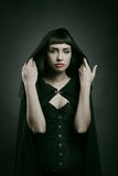 Beautiful pale woman with black cloak. Dark fantasy and halloween Royalty Free Stock Photo