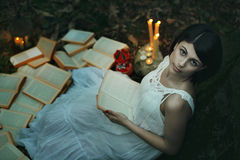 Beautiful pale woman in a dark forest. Beautiful pale woman among open books in a dark forest. Surreal and weird stock images