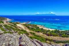 Blue sea and Athos mountain in Greece. Beautiful panorama of the Aegean Sea, with rocks and green vegetation, and Mount Athos in background Royalty Free Stock Image