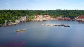 Blue sky reflects in artificial lake in clay quarry pit. Beautiful panorama boundless blue sky reflects in artificial lake with small islands in clay quarry pit stock footage