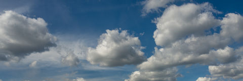 Beautiful panorama of fluffy white clouds in blue sky Stock Images