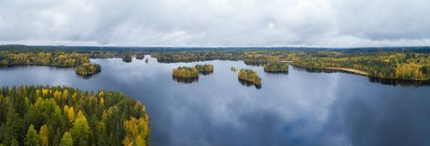 Beautiful panorama of the lake and green forest, aerial landscape. Cloud reflection on water. Environment concept. Finnish nature.