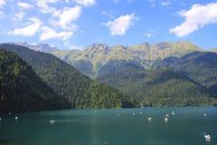 Beautiful panorama Lake Riza. Beautiful panorama of natural mountain landscape. Pleasure boats on the water. Blue Lake Ritsa among mountains of the Caucasus Royalty Free Stock Image