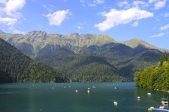 Beautiful panorama Lake Riza. Beautiful panorama of natural mountain landscape with clouds. Pleasure boats on the water. Blue Lake Ritsa among mountains of the Stock Photos