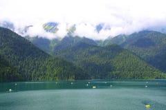 Beautiful panorama Lake Riza. Beautiful panorama of natural mountain landscape with low clouds. Blue Lake Riza among mountains of the Caucasus, Abkhazia. Ritz Royalty Free Stock Photography