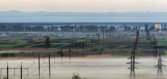 Beautiful panorama of long electric high voltage power line rows. Stretching to horizon through spring fields and trees under dense morning fog on distant Royalty Free Stock Photography