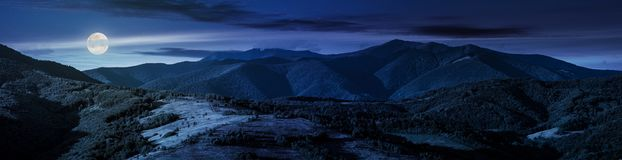 Beautiful panorama of mountain ridge at night. In full moon light. wonderful landscape in early autumn Royalty Free Stock Image