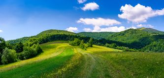 Beautiful panorama of mountainous countryside. Lovely summer scenery in fine weather condition. rural fields at the edge of a forest on hillside. road down the Stock Photos