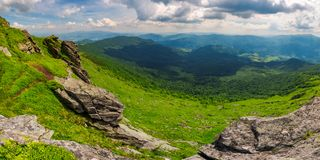 Beautiful panorama of mountainous landscape. View from the edge of a hillside with cliffs. Borzhava ridge and Runa mountain in the distance. village down in Royalty Free Stock Images
