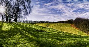 Beautiful panorama of rolling hills, green grass and blue sky Stock Image