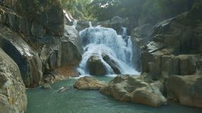 Strong Waterfall Streams into River between Cliffs. Beautiful panorama strong waterfall streams with foam between sharp cliffs to green river among tropical stock video footage