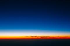 Beautiful panorama of sunset from height of airplane. Dark sunri Royalty Free Stock Photo