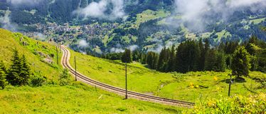 Beautiful Panorama of Swiss mountain pass railway track passing traditional Swiss mountainous village view from Murren-Gimmelwald. Trail, Jungfrau Region Royalty Free Stock Photography