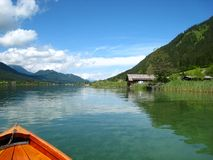 Wonderfully panorama view with a turquoise blue austrian lake with green mountains and wooden houses. Beautiful panorama view with a turquoise blue austrian lake royalty free stock photos