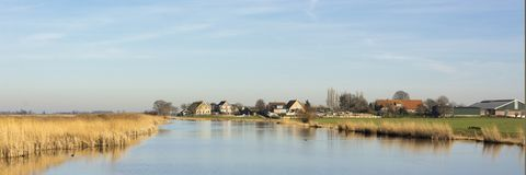 Beautiful panorama view on a typical dutch landscape. Water, reed and a tiny village in Het Groene Hart in the Netherlands. A beautiful quiet rural area in a stock photography