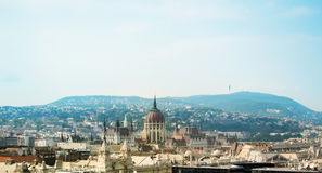 Beautiful panoramic aerial view over the roofs of Budapest, old orange tile roofs and Parliament building with blue hills and fore Royalty Free Stock Photos