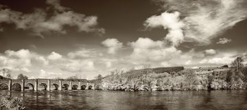 Beautiful panoramic landscape with an old stone bridge on a sunn Royalty Free Stock Photography