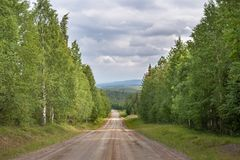 A beautiful panoramic macadam road through the forest in Finland. stock photo