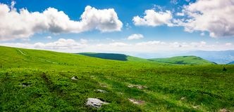 Beautiful panoramic mountainous landscape. Lovely summer scenery of grassy hills under the  blue sky with clouds Royalty Free Stock Photo