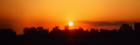 Beautiful panoramic natural background. Silhouettes of trees against the backdrop of the setting sun and the orange sky. Fashion backdrop stock photos