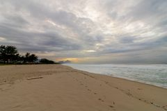 Beautiful panoramic sunrise on the beach of Barra da Tijuca with the stone of Gávea in the background stock photos