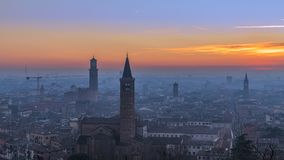 Beautiful panoramic sunset view of old town of Verona, Torre Lamberti and Santa Anastasia bell tower covered with evening fog. royalty free stock image