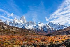 Beautiful panoramic view of Fitz roy mountains with white snow peak with colorful red orange leaves tree in sunny blue sky day,. Autumn, El Chalten, south stock image