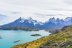 Beautiful panoramic view of golden grass and aqua blue Pehoe lake with small island with nature cuernos mountains peak with cloud. In autumn, Torres del Paine stock image