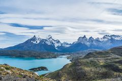 Beautiful panoramic view of golden grass and aqua blue Pehoe lake with small island with nature cuernos mountains peak with cloud. In autumn, Torres del Paine stock photography