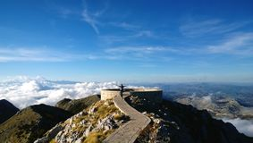 Beautiful panoramic view at the memorial njegoš in Montenegro: a girl stands with her hands raised at high altitude. Beautiful panoramic view at the Royalty Free Stock Image