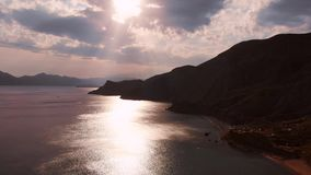 Beautiful panoramic view of the mountains and the sea, filming from above. Aerial shooting from the shoreline on an. Overcast day, the sun`s rays make their way stock video footage