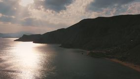 Beautiful panoramic view of the mountains and the sea, filming from above. Aerial shooting from the shoreline on an. Overcast day, the sun`s rays make their way stock footage