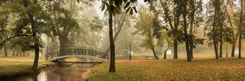 Free Beautiful Panoramic View Of The Autumn City Park With A Pedestrian Bridge Over A Shallow Stream With A Slight Haze From The Stock Image - 160775781