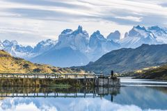 Beautiful panoramic view small people standing at the dock from the lake with Cuernos, horn mountains peak with lenticular cloud. In autumn, Torres del Paine stock images