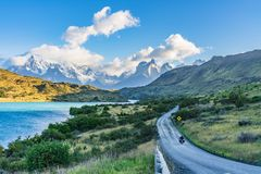 Beautiful panoramic view of stone road with aqua blue Pehoe lake and background of nature cuernos mountains peak with cloud in. Autumn, Torres del Paine royalty free stock photography