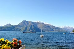 View to the lake Como from Bellagio, to a passenger ship moving and mountains covered with snow in background. royalty free stock photography