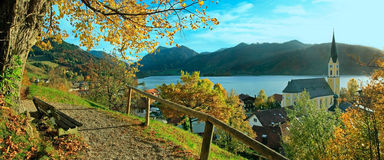 Beautiful panoramic view to schliersee village in autumn. Lookout point with bench and lime tree in october stock photography