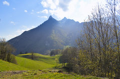 Beautiful paradise in Switzerland, Gruyeres. Amazing landscape in Gruyeres, Swiss, Europe. Mountain, green fields and blue sky with sun. Image taken in midday Stock Photography