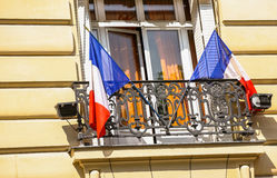 Beautiful Parisian building and French flags Royalty Free Stock Photography