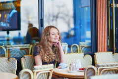 Beautiful Parisian woman in cafe. Drinking coffee and eating macaroons, traditional French dessert Stock Photography