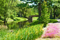 Beautiful park landscape with river, bridge and flowers Royalty Free Stock Photos