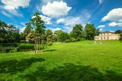 Beautiful park in spring with little castle on green hill. In front of blue sky with white clouds royalty free stock photography
