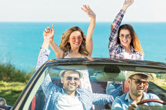 Beautiful party friend girls dancing in a car on the beach happy Stock Images